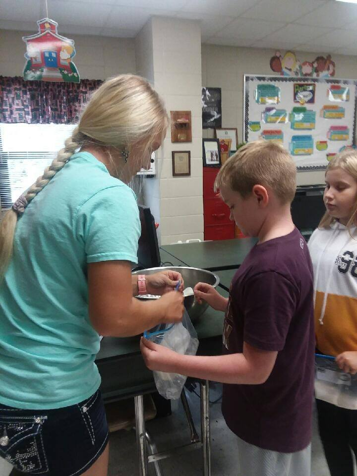 Mrs. Hoelscher helping a student with his ice cream
